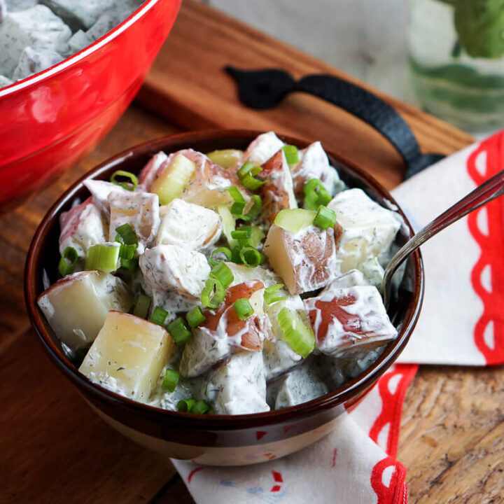 A bowl of cream red potato salad on a serving tray.