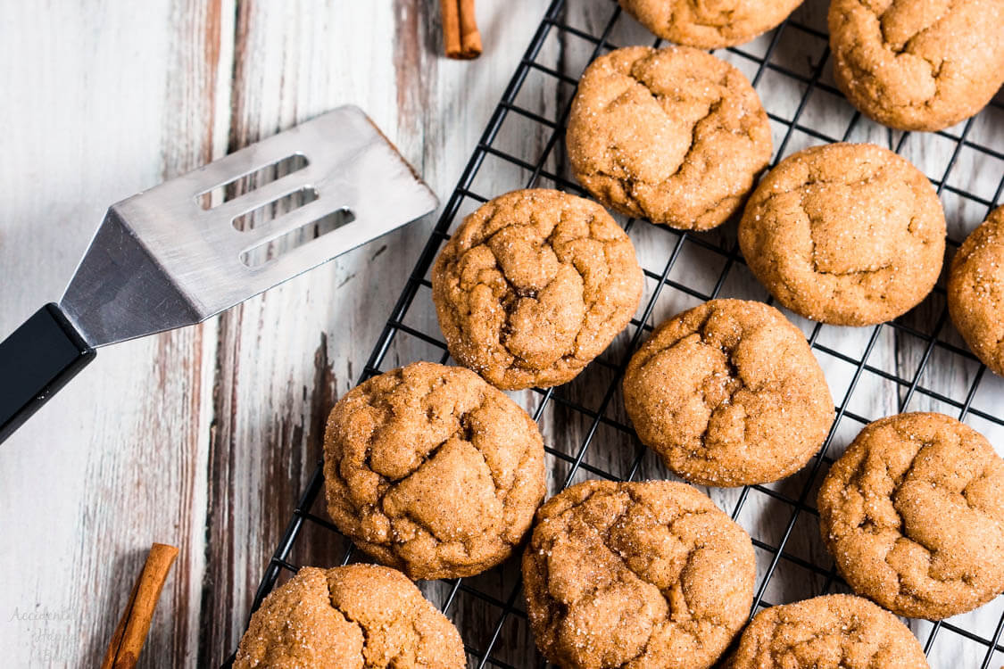 Several pumpkin gingersnap cookies set on a cooling rack.