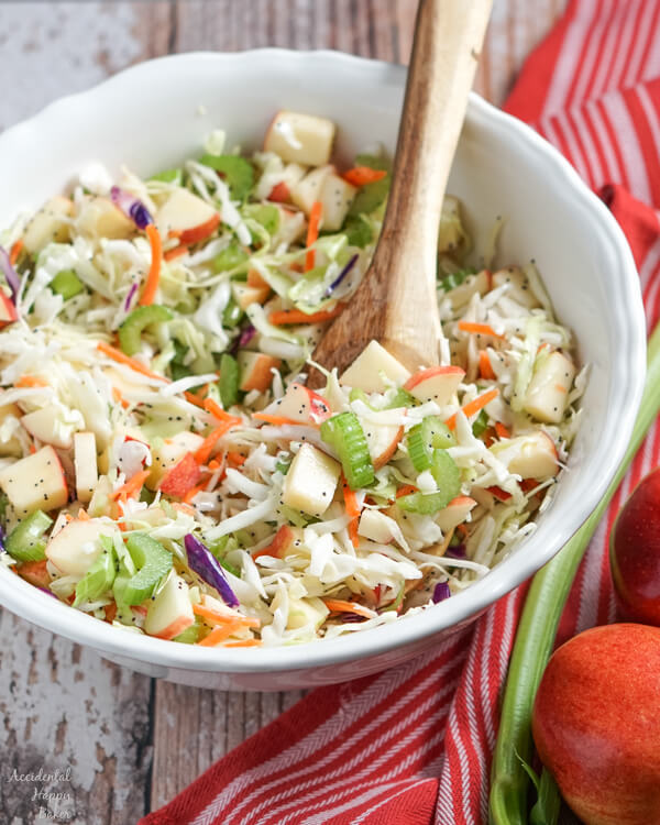 A large white serving bowl full of apple coleslaw.