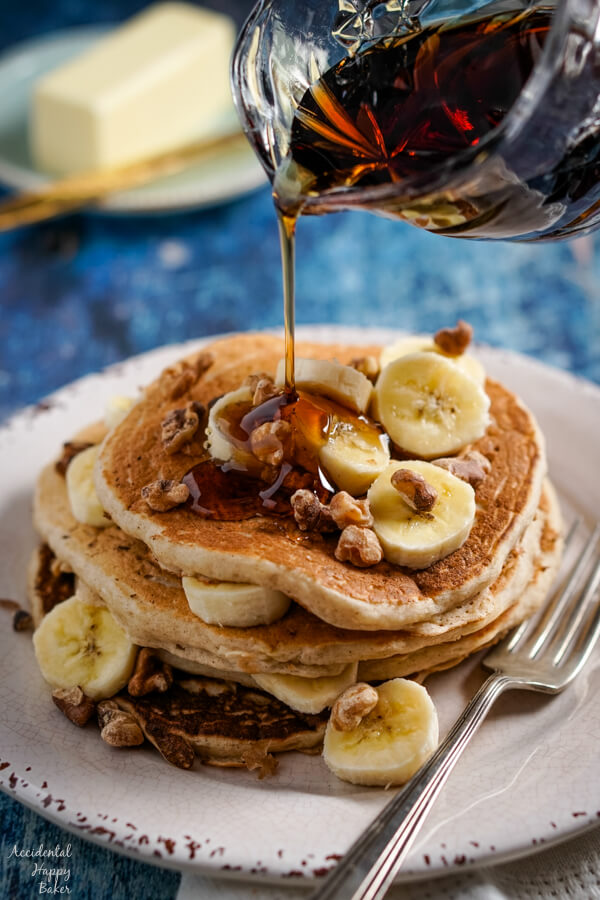 Maple syrup is poured over a stack of banana pancakes.