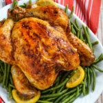 A roasted chicken rests on a bed of green beans with lemons on a white platter.
