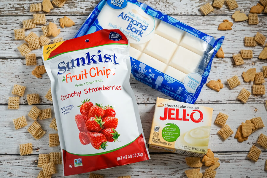 Freeze dried strawberries, almond bark and cheesecake pudding on a wood background with cereal sprinkled around it.