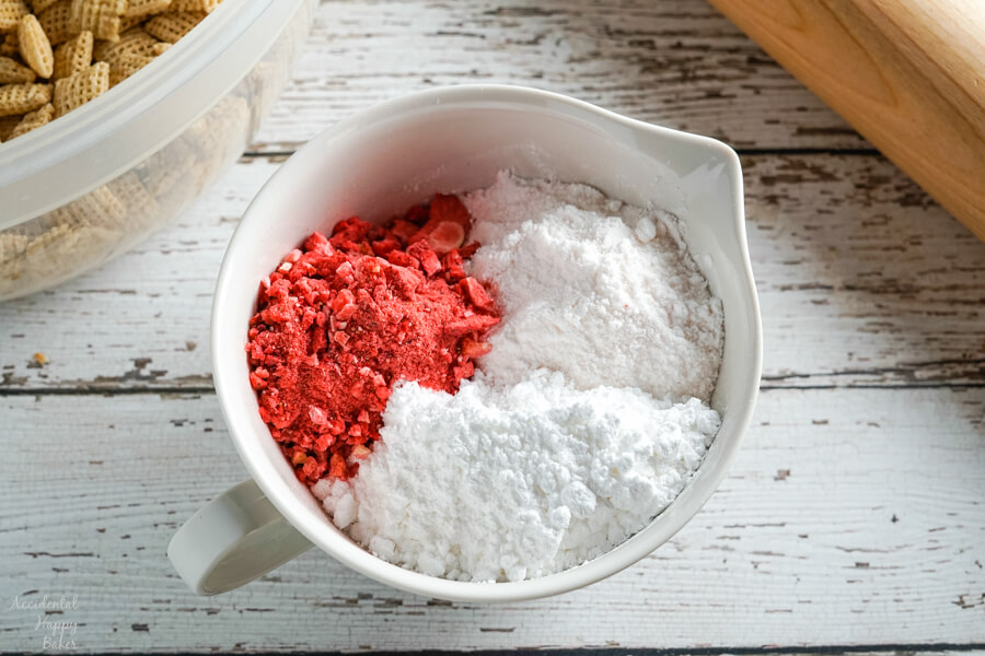 A bowl full of the coating for Strawberry Cheesecake muddy buddies.