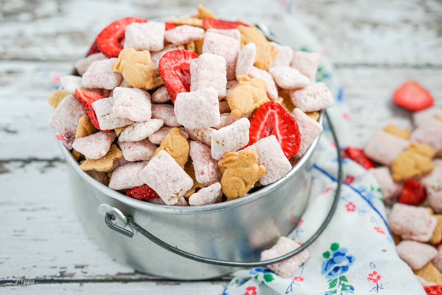 A silver bucket full of strawberry cheesecake muddy buddies with a blue flowered napkin beside it.