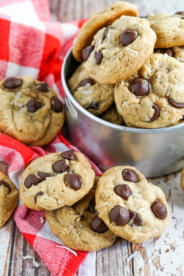 Chewy Coconut Chocolate Chip cookies stacked on a red checked towel and nestled in a metal bucket.