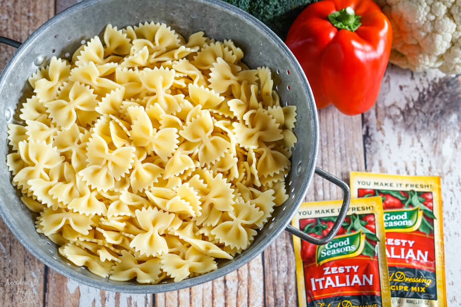 A colander of cooked pasta next to a pile of veggies and 2 packets of Italian dressing mix.