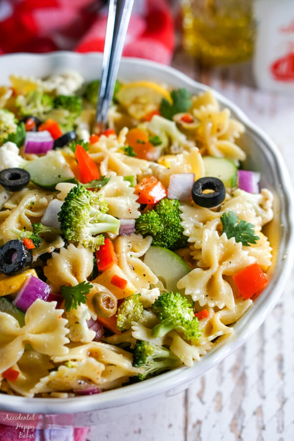 A vertical photo of a white bowl with summer vegetable pasta salad with a serving spoon.