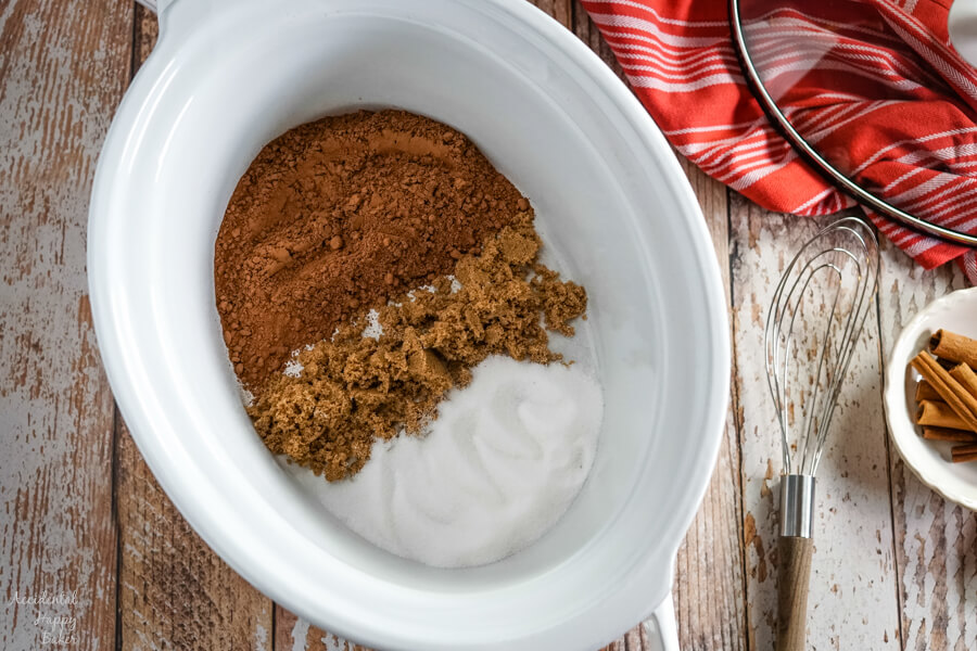 A white slow cooker with cocoa powder, brown sugar and granulated sugar next to a whisk.