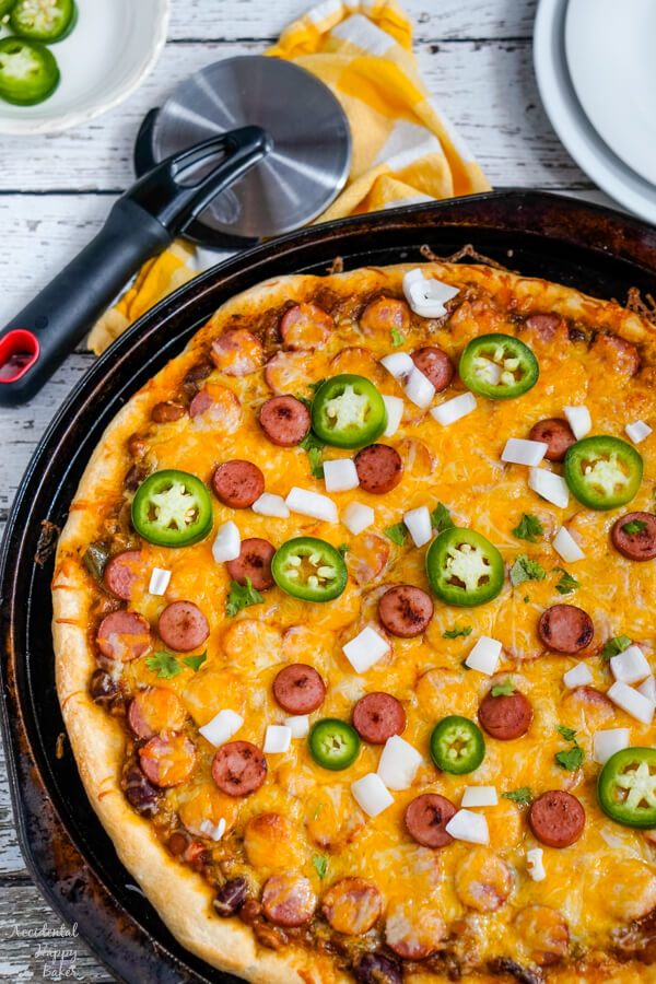 A freshly baked chili dog pizza with a pizza cutter set nearby.