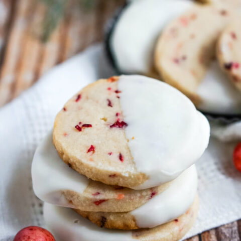 A stack of White Chocolate Cranberry Shortbread Cookies sitting on a white napkin with a cranberry to one side.