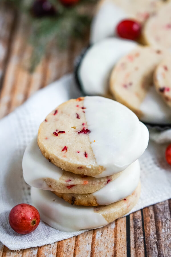 A stack of shortbread cookies on a white napkin next to some fresh cranberries.