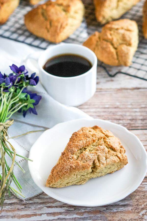A scone on a white plate sitting in front of a cup of Earl Grey tea.