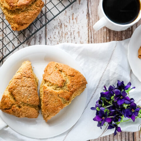 Two Earl Grey Scones on a plate sitting by a wire cooling rack full of fresh baked scones.