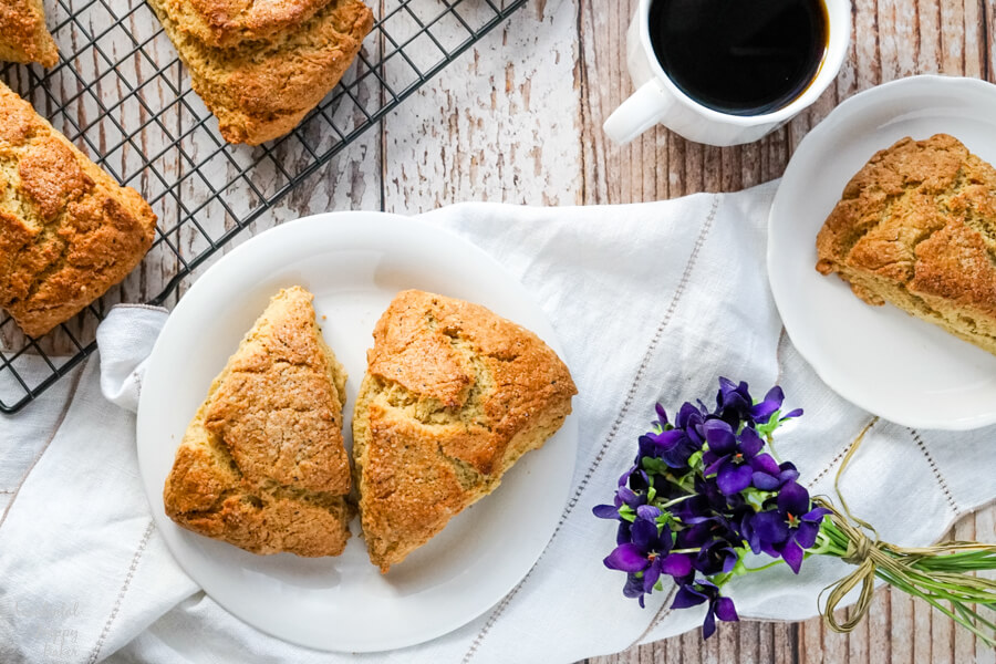 Two scones on a white plate next to a wire rack full of scones.