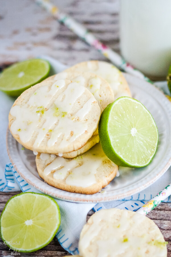 Key Lime Shortbread Cookies stacked on a white plate with slices of lime.