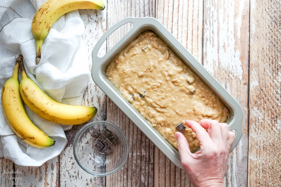 A loaf pan full of banana bread batter as more chocolate chunks are added to the top.