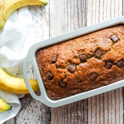 A loaf pan of freshly baked chocolate chunk banana bread.
