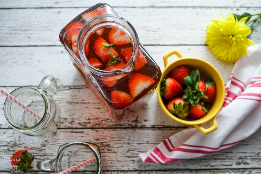 A pitcher of strawberry basil iced tea next to a yellow bowl full of strawberries.