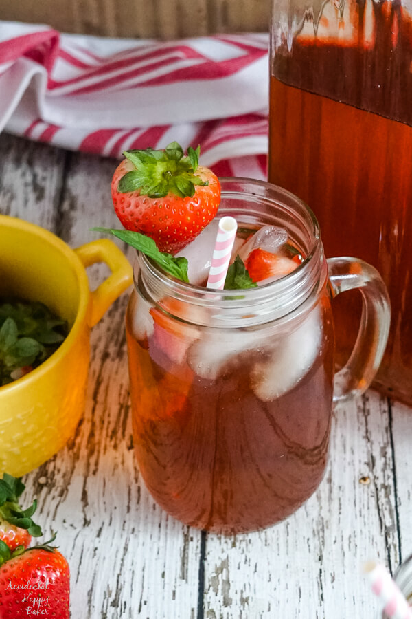 A mason jar cup of strawberry basil iced tea sitting next to a pitcher.