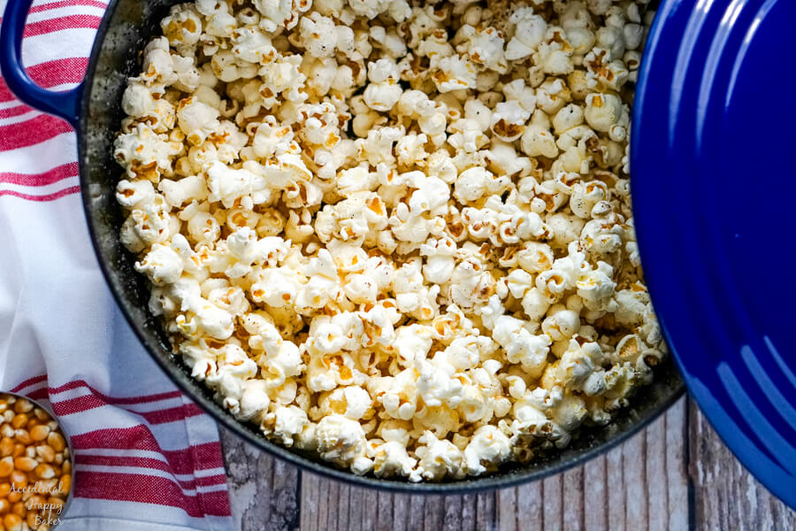 A blue dutch oven full of freshly popped popcorn.