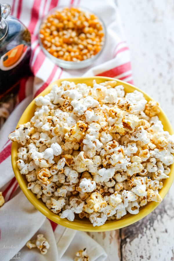 A bowl of kettle corn with some unpopped kernels and maple syrup in the background.