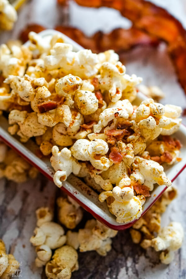 A close up image of a bowl of popcorn with bacon pieces and other seasonings.