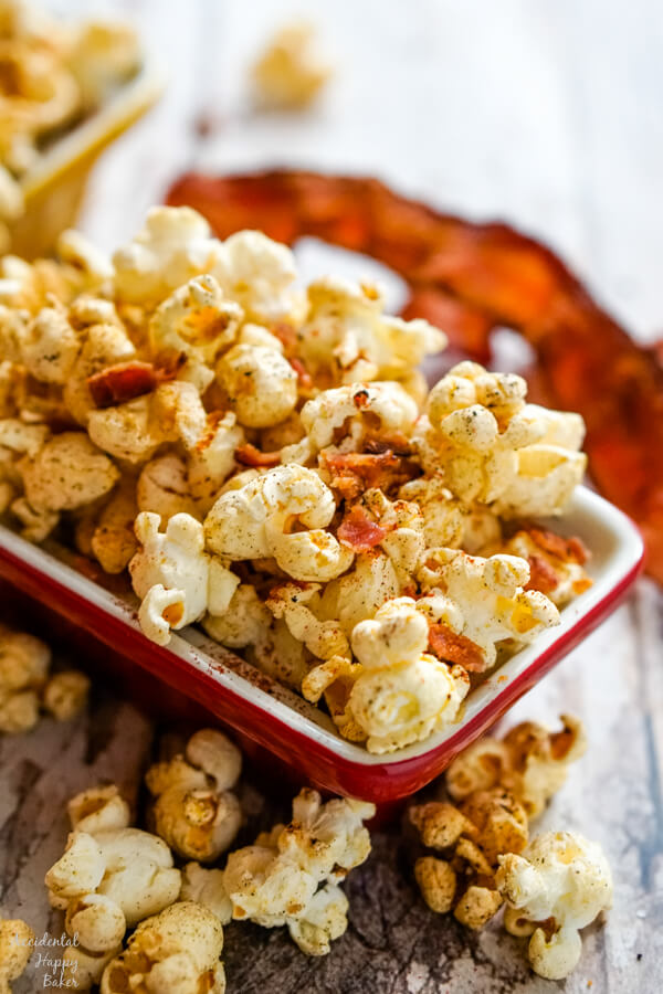A red bowl full of popcorn with a piece of bacon in the background.