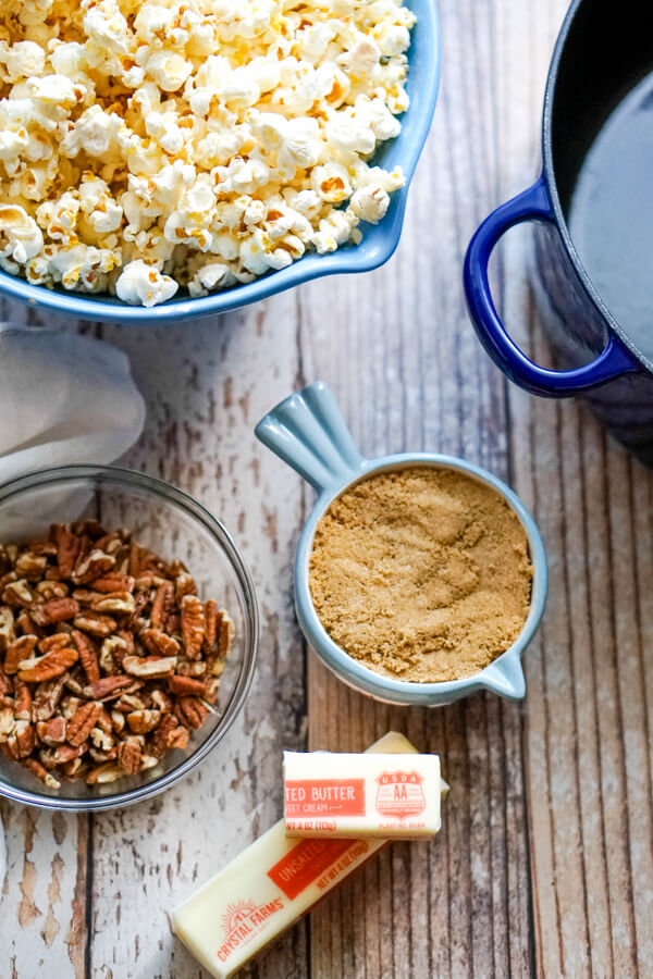 A bowl of popped popcorn next to pecans, brown sugar, and butter.