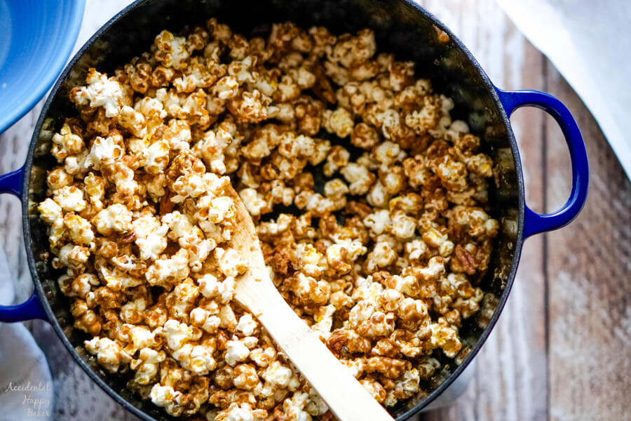 A blue dutch oven of caramel corn with a wooden spoon.