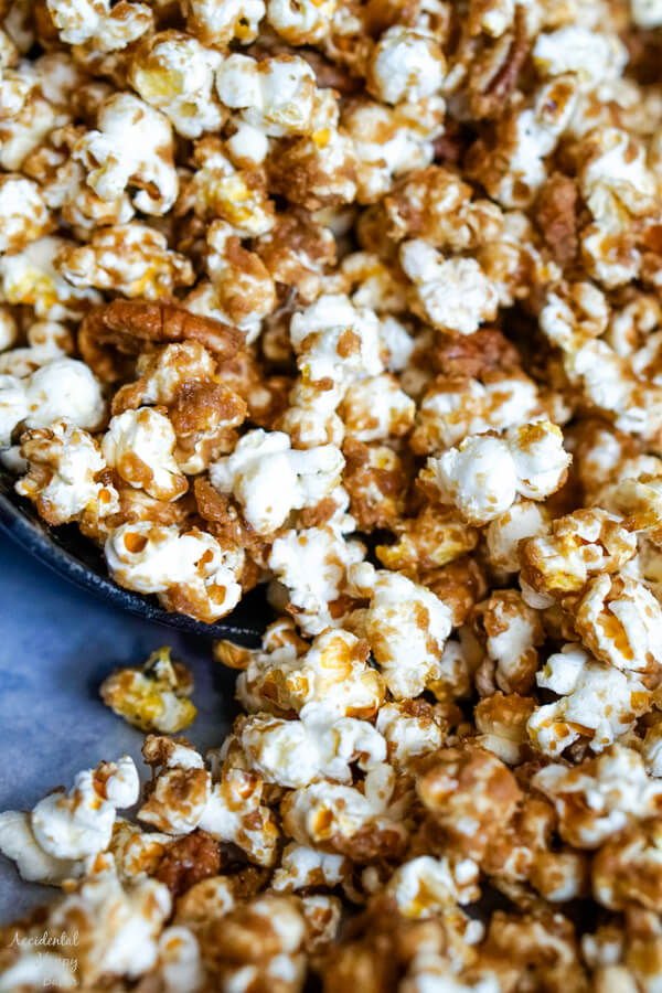 A close up image of the popcorn that shows the texture of the caramel on the popcorn and pecans.