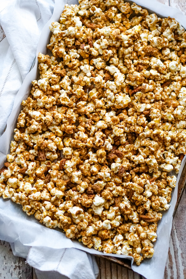 The caramel corn is spread out on a lined cookie sheet to let cool.
