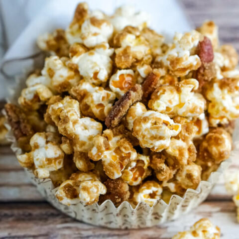 A paper cup with a serving of Salted Caramel Pecan Popcorn