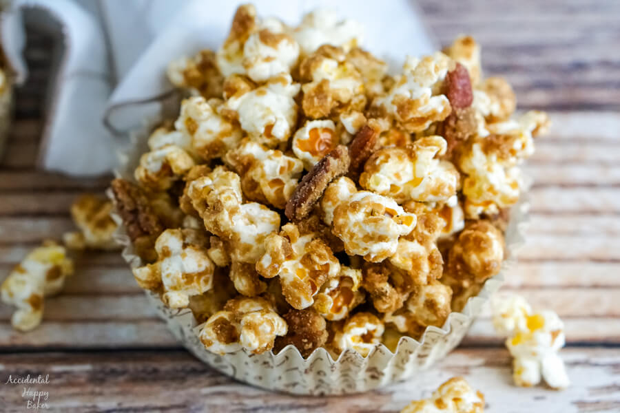 A serving of caramel corn in a paper cup.