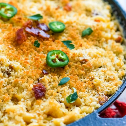 A close up image that shows the browned bread crumbs, bacon and jalapenos topping the macaroni and cheese.