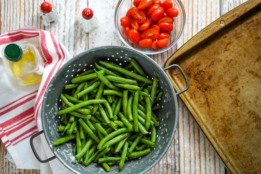 Green beans in a metal colander, next to a bowl of tomatoes, olive oil, salt and pepper.