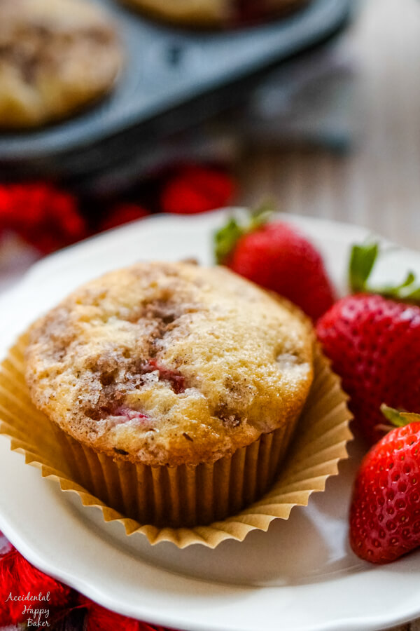A strawberry rhubarb muffin on a plate with 3 strawberries.
