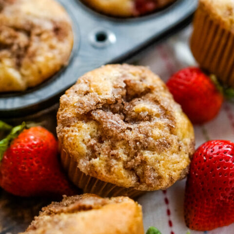 A close up shot of a strawberry rhubarb muffin next to a muffin tin and some fresh strawberries.
