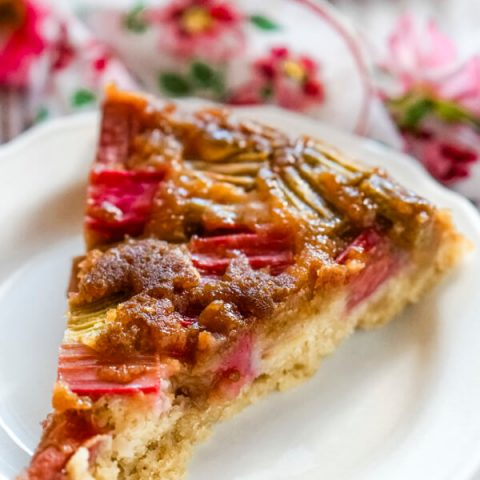 A slice of rhubarb ginger upside down cake on a white plate.