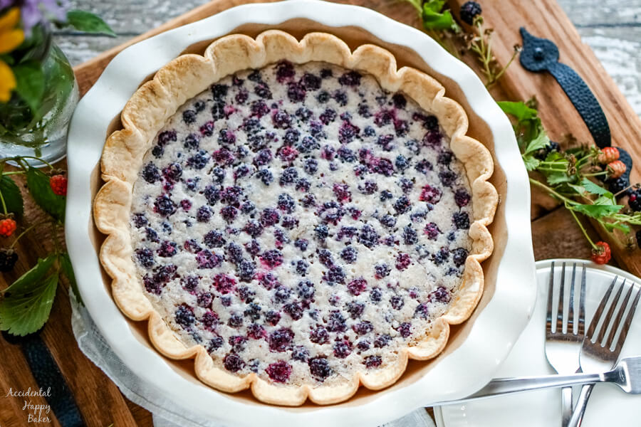 A full blackberry pie in a white pie pan on wooden tray surrounded by blackberries.