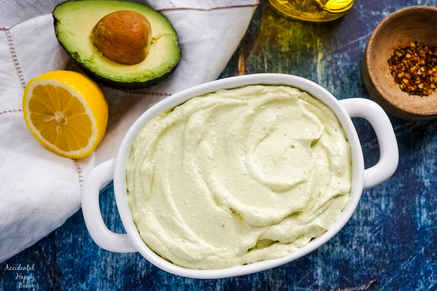 A bowl of lemon feta dip sitting next to half an avocado and lemon.