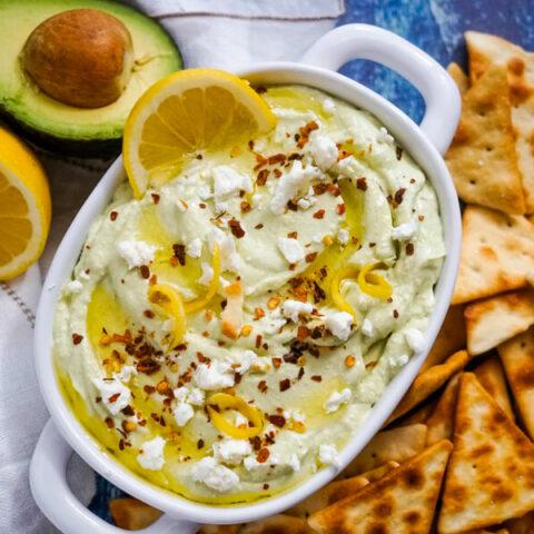 A white serving bowl of lemon feta dip surrounded by pita chips.
