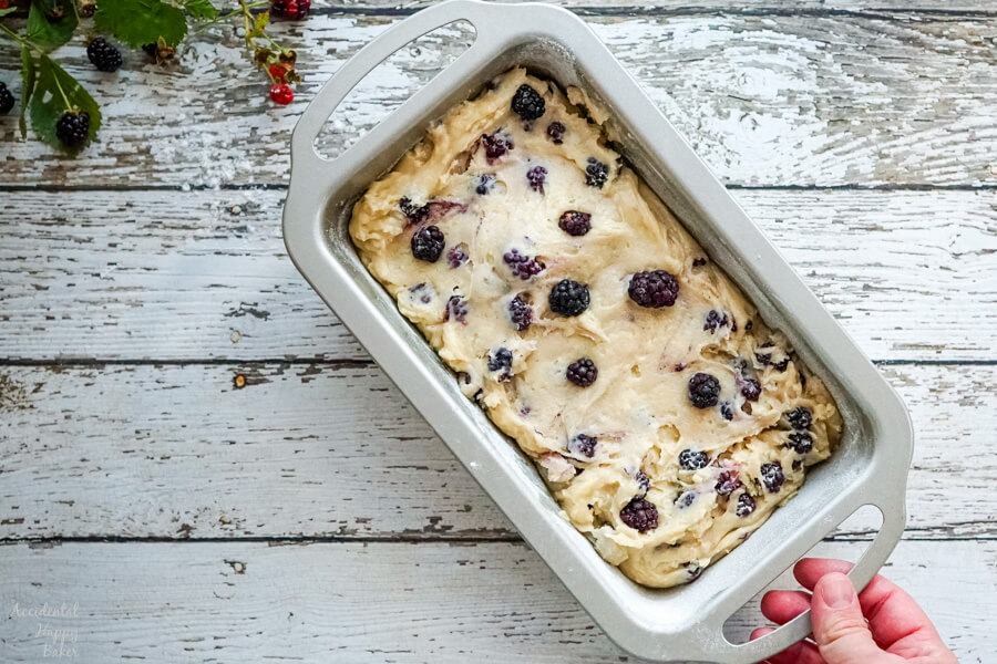 A silver loaf pan of blackberry bread batter ready to be baked.