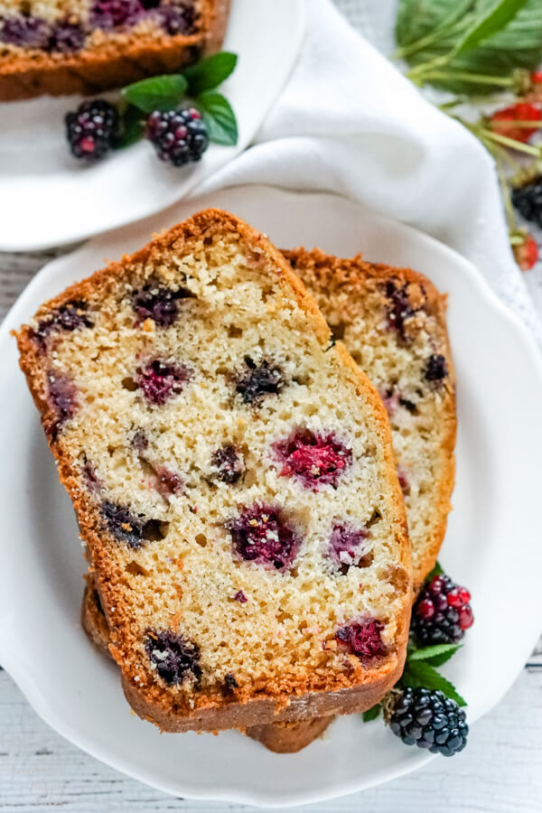 Two slices of blackberry bread on a white plate with fresh blackberries by the side.