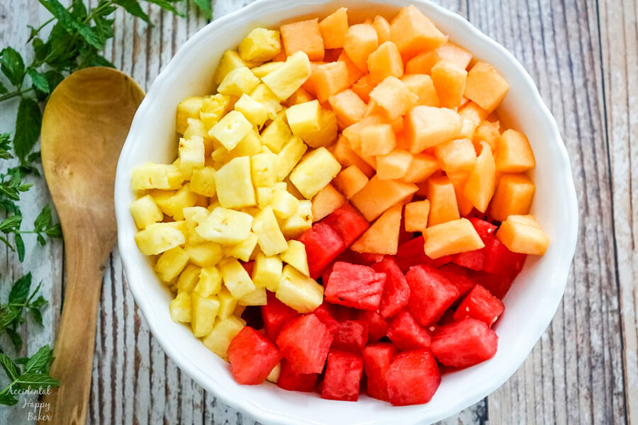 A large white bowl full of chopped watermelon, cantaloupe and pineapple