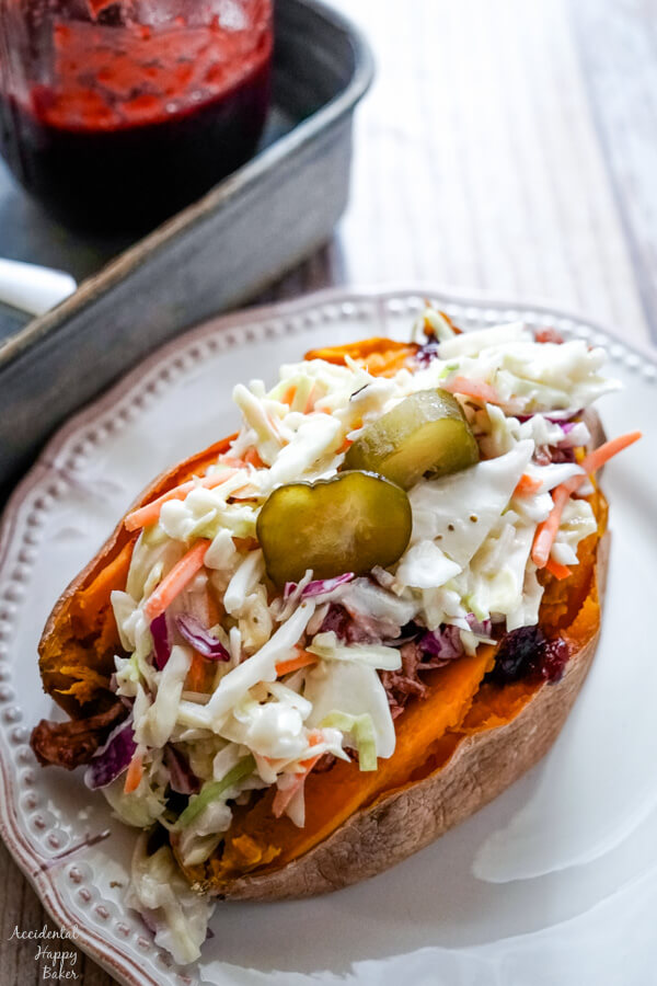 A baked sweet potato stuffed with bbq chicken and coleslaw on a white plate.